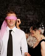 Senior adult woman adjusting scarf covering young adult man's eyes Stock Photos