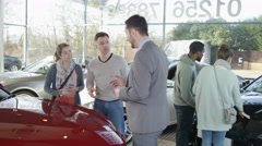 4K Salesman in car dealership showing couple new car & shaking hands on a deal - stock footage