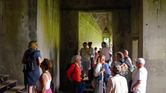 Tourists pause for a break inside a corridor in Angkor Wat. Video 3840x2160 Stock Footage