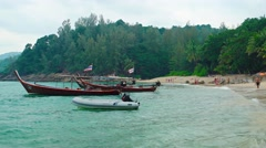 Traditional longtail boats tied to a tropical beach, with sound. Video UltraH Stock Footage