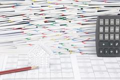Stock Photo of House with pencil and overload of confused paperwork as background