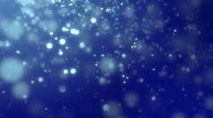 White luminous particles falling against dark blue background Stock Footage