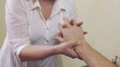 Close up of masseuse hands make massage of hand wrist to adult man. Healing Stock Footage