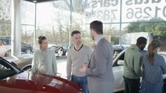 4K Salesman in car dealership showing couple new car & shaking hands on a deal Stock Footage
