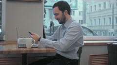 Successful young businessman using cell telephone during coffee break in cafe Stock Footage