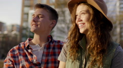 Cute Couple Sit On Park Bench In City, Man Tells His Girlfriend A Funny Story Stock Footage