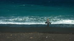 Balinese woman collect sea water on black volcanic sand beach Stock Footage