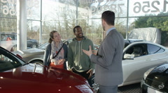 4K Salesman in car dealership with couple, showing them the engine of new car Stock Footage