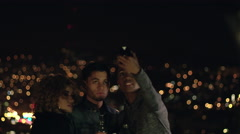Three friends at a party take selfie on the balcony in front of the city lights Stock Footage