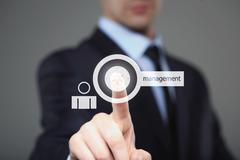 Businessman pressing button on touch screen interface and select management - stock photo