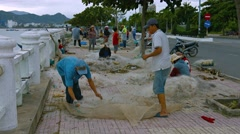 Local fishermen begin their work day by straightening their nets on the quay. Stock Footage