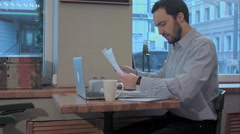 Tired young bearded businessman in a cafe prepareing for meeting Stock Footage