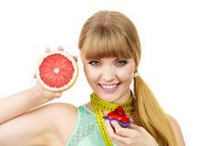 Stock Photo of Woman choosing fruit or cake make dietary choice