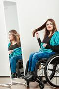 Invalid girl on wheelchair combing hair - stock photo