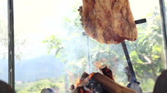 From the bottom shot of argentinian asado sizzling on embers. Barbecued meat. - stock footage
