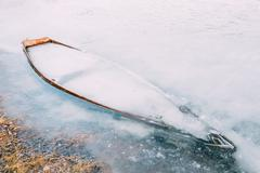 Frozen into ice of river, lake, pond old wooden boat. Forsaken r - stock photo