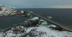 Droneshot Of A Bridge On Lofoten Islands With Snowcovered Rocks Around Stock Footage
