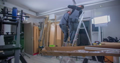 Two handymen are standing with their ladders close to each other and checking Stock Footage