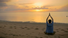 A man sits in a lotus pose facing the ocean during sunrise Stock Footage
