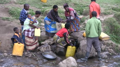 Local residents collect water in a single source of water near the village Stock Footage