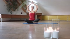 Young female in lotus pose raising hands Stock Footage