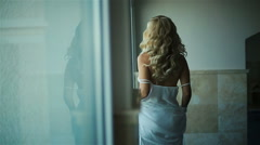 Sexy blond bride watching aside on white short robe back view Stock Footage