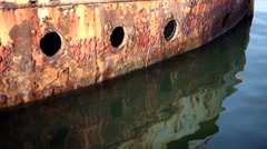 Locked down shot of rusty hull with portholes of a shipwreck sinking in the sea. Stock Footage