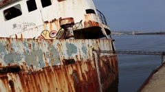 Locked down shot of a shipwreck with colored graffiti sinking in the sea. Stock Footage