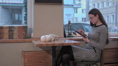 girl in cafe uses small mobile computer - stock footage