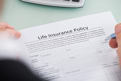 Close-up Of Person Filling Life Insurance Policy Form Stock Photos