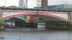 Boat floating under the Blackfriars Bridge in London Stock Footage
