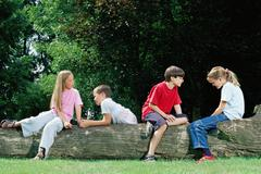 Boys and girls sitting on a log - stock photo