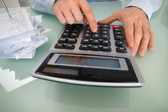 Close-up Photo Of Businessperson Using Calculator To Calculate Tax Stock Photos