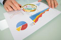 Businessman Analyzing Graph Through Magnifying Glass In Office Stock Photos
