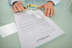 Person's Hand Looking At Contract Through Magnifying Glass - stock photo