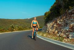 Woman cyclist riding a bike on a mountain road Stock Photos