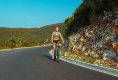 Woman cyclist riding a bike on a mountain road - stock photo