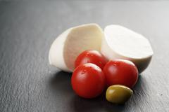 Sliced mozarella ball with tomato and olives on slate background Stock Photos