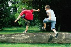 Boys jumping over a log Stock Photos