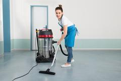 Happy Young Female Janitor Cleaning Floor With Vacuum Cleaner Stock Photos