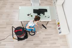 Young Female Janitor Cleaning Wooden Floor With Vacuum Cleaner - stock photo