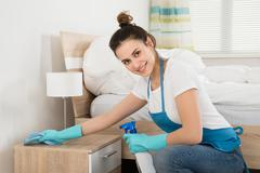 Happy Female Housekeeper Cleaning Nightstand In Room Stock Photos