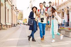 Three happy friends walking during sightseeing - stock photo