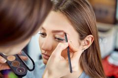 young, beautiful girl apply makeup on a eyebrows in a beauty salon - stock photo