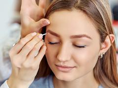 Beautiful young girl got correction of eyebrows in a beauty salon - stock photo
