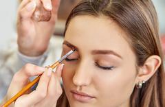 Beautiful young girl dyed her eyebrows in a beauty salon - stock photo