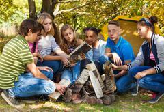 International teens setting up bonfire together - stock photo