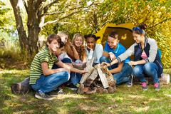 Happy teens sett up bonfire together on campsite Stock Photos