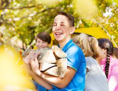 Laughing boy holding kindling wood on campsite - stock photo