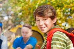 Close-up of boy with rucksack near yellow tent - stock photo